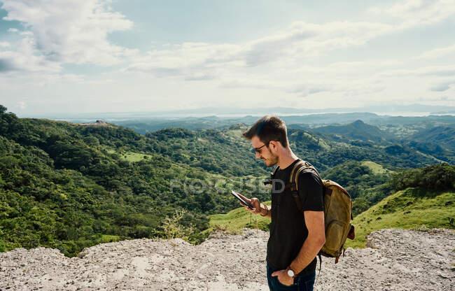 Vista laterale dell'escursionista maschio concentrato con messaggi di testo sullo zaino sul cellulare durante il trekking in località di montagna in Costa Rica — Foto stock