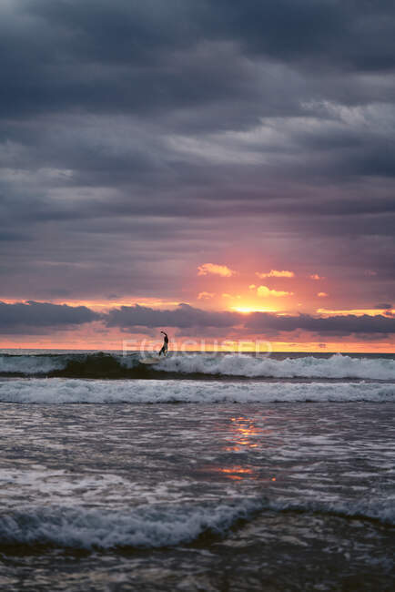 Unrecognizable man with surfboard walking near waving sea in cloudy evening on beach in Costa Rica — Stock Photo