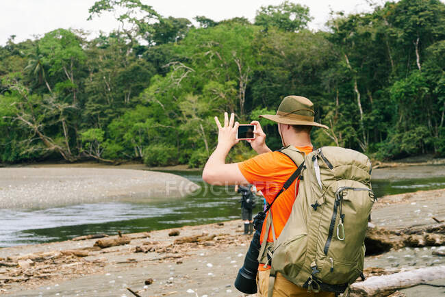 Back view of anonymous male tourist with backpack taking photos on cellphone while standing on shore in Costa Rica — Stock Photo