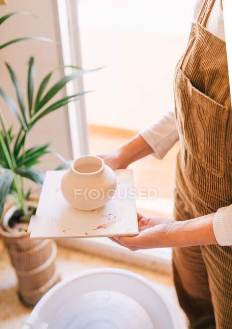 Высокий угол у кустарницы в повседневной одежде с маленькой бежевой керамической вазой на квадрате противостоит размытому интерьеру светлой современной квартиры — стоковое фото
