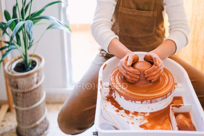 Высокий угол наклона человека в повседневной одежде, делающего керамику ручной работы с использованием специального оборудования во время работы в светлой современной студии — стоковое фото