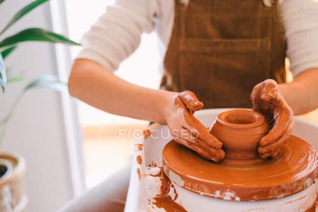 Hohe Winkel der Ernte Person in lässiger Kleidung machen handgemachte Keramik mit speziellen Geräten während der Arbeit in Licht zeitgenössischen Studio — Stockfoto