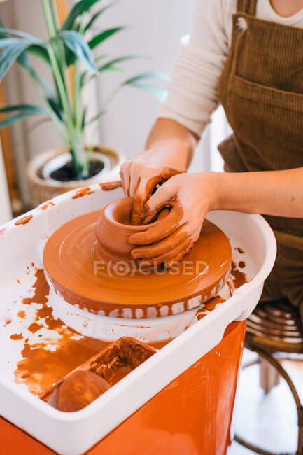 High angle of crop person in casual clothes making handmade pottery using special equipment while working in light contemporary studio — Stock Photo