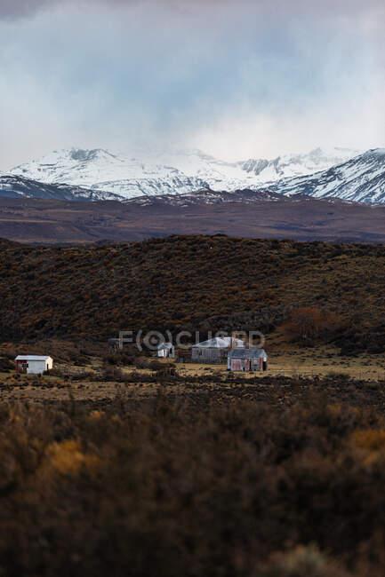 Paesaggio incredibile con case di campagna solitarie ai piedi contro cime innevate all'orizzonte sotto il cielo nuvoloso — Foto stock