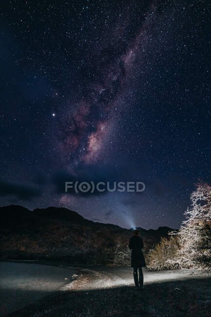 Back view of person standing with light on lake shore under clear starry sky against dark silhouette of hills at silent night — Stock Photo