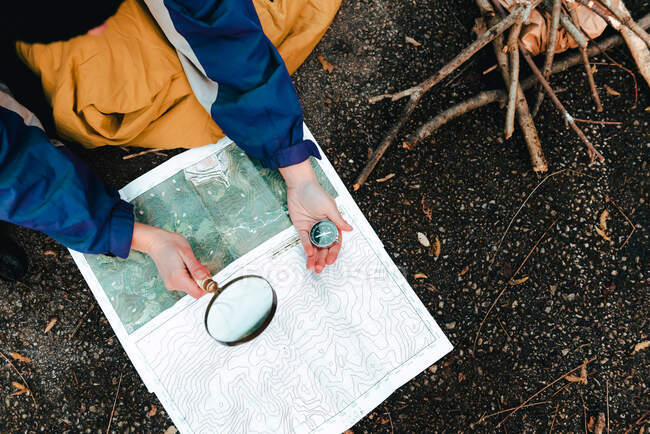 Unrecognizable hiker navigating with map and compass in countryside — Stock Photo