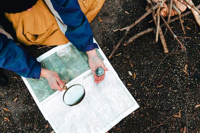 Unbekannter Wanderer navigiert mit Karte und Kompass in der Natur — Stockfoto