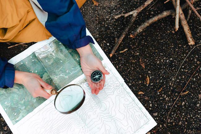 Dall'alto il viaggiatore del raccolto controlla il percorso sulla mappa topografica con bussola e lente d'ingrandimento mentre è seduto a terra in autunno giorno — Foto stock