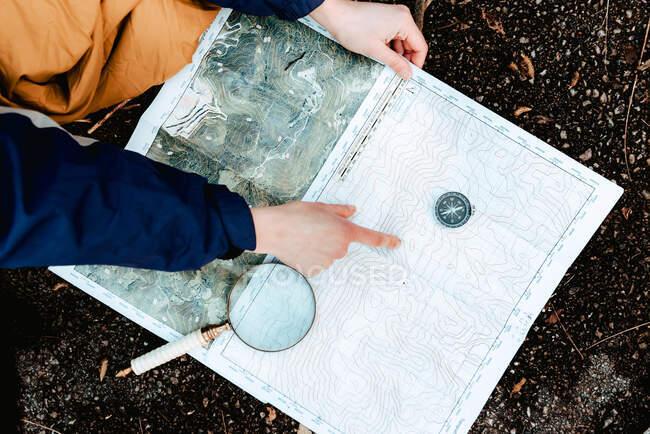 Caminante irreconocible navegando con mapa y brújula en el campo - foto de stock