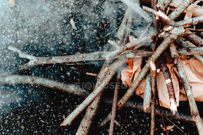 From above closeup smoke and flaring up fire from wooden sticks and branches on ground — Stock Photo