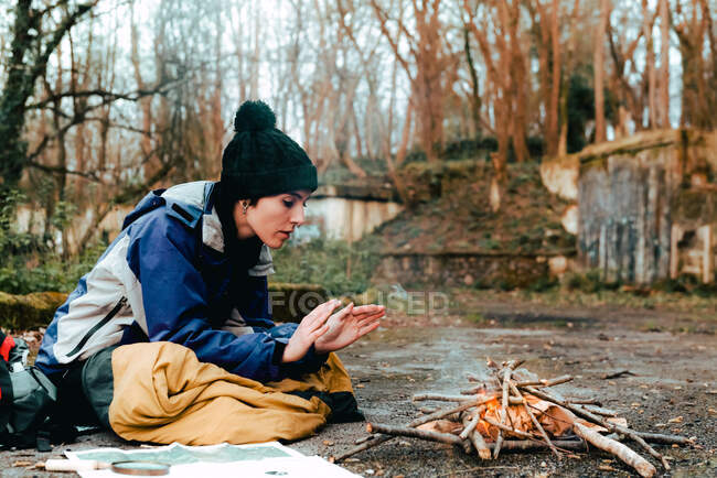 Side view of young female camper in warm clothes warming hands at bonfire while sitting on ground in countryside in autumn day — Stock Photo