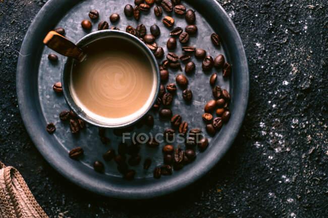 Vista superior de granos de café y taza con café fresco y cuchara colocada en bandeja de metal en la mesa áspera - foto de stock
