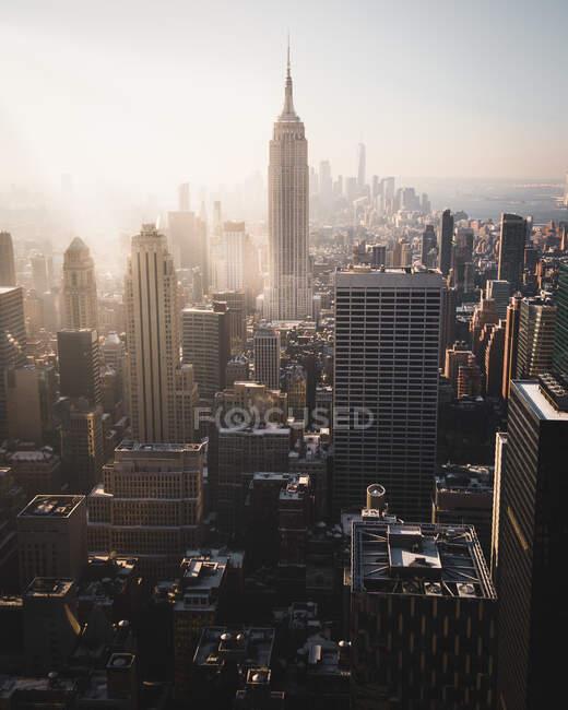D'en haut de grands gratte-ciel modernes avec des murs de lunettes contre le ciel bleu et le soleil à New York — Photo de stock