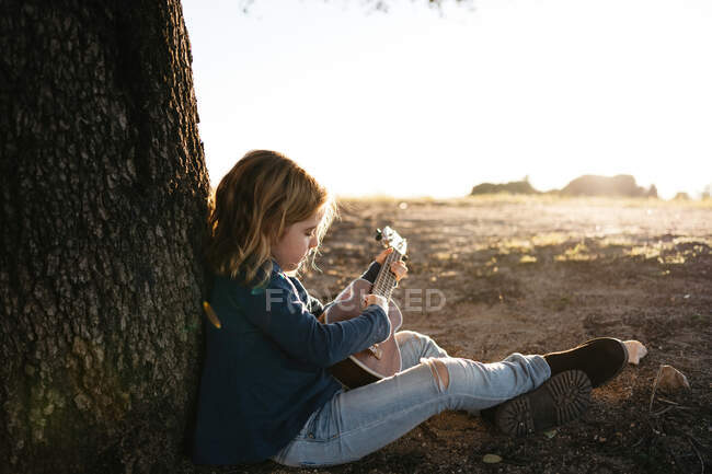 Біля прекрасної серйозної дівчинки в повсякденному одязі грає на гітарі укулеле, сидячи біля дерева в сонячний літній день у сільській місцевості. — стокове фото