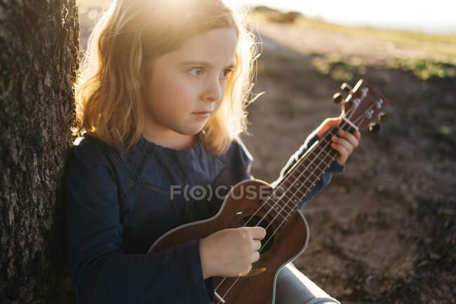 Приваблива серйозна дівчинка в повсякденному одязі грає на гітарі укулеле, сидячи біля дерева в сонячний літній день у сільській місцевості. — стокове фото