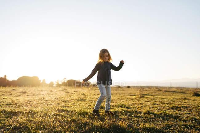 Adorabile bambina attiva in abbigliamento casual che gioca e balla nel campo verde mentre si gode la soleggiata serata estiva in campagna — Foto stock