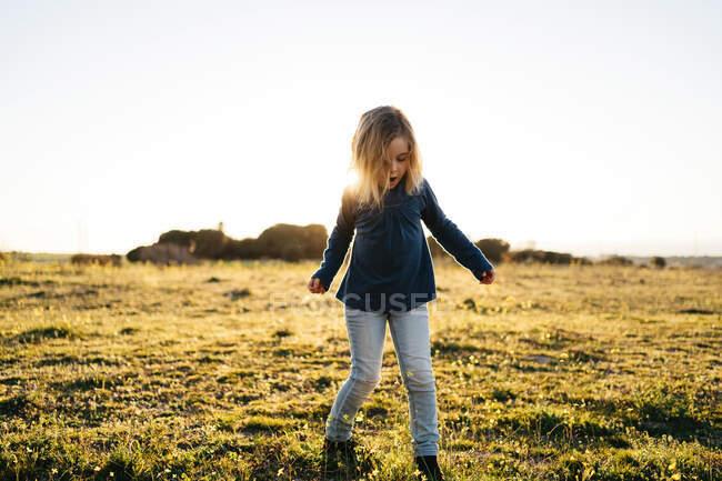 Adorable niña activa en ropa casual jugando y bailando en el campo verde mientras disfruta de la soleada noche de verano en el campo - foto de stock