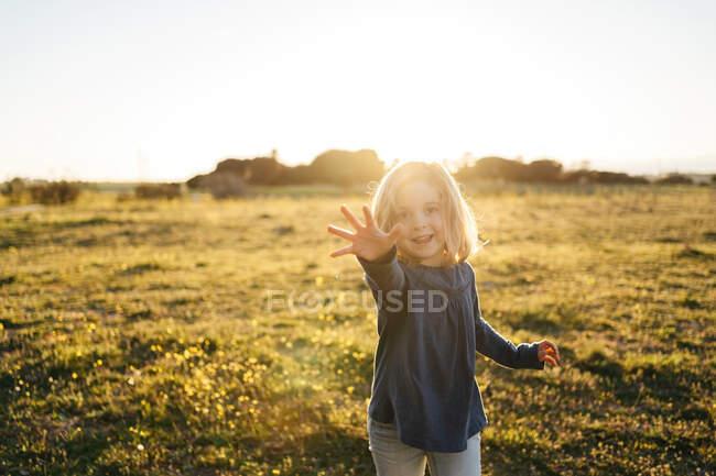 Linda niña en ropa casual con el brazo extendido mirando a la cámara con sonrisa y mostrando cinco mientras está de pie en el prado verde durante el atardecer de verano - foto de stock