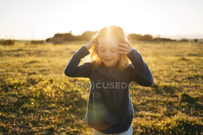 Cute little girl in casual wear with smile looking down while standing on green meadow during summer sunset — Stock Photo