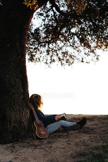 Vista laterale di calma anonima bambina in abbigliamento casual lettura libro di fiaba mentre seduto sotto l'albero in campo nella giornata di sole con ukelele al suo fianco — Foto stock