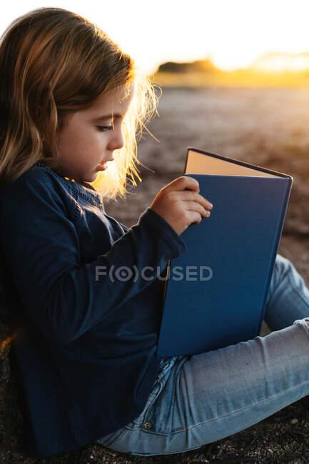Vue latérale d'une petite fille calme en tenue décontractée lisant un livre de contes de fées assis sous un arbre dans un champ lors d'une soirée d'été ensoleillée — Photo de stock