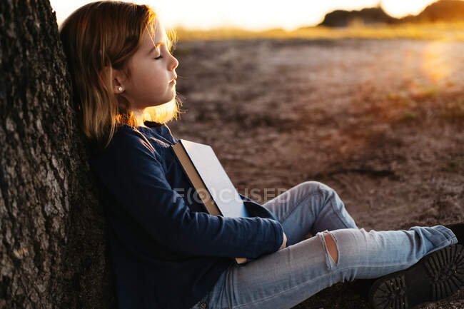 Side view of calm little girl in casual wear with closed eyes holding a fairy tale book while sitting under tree in field in sunny summer evening — Stock Photo