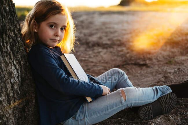 Vue latérale d'une petite fille calme en tenue décontractée regardant la caméra lire un livre de conte de fées tout en étant assis sous un arbre dans un champ dans une soirée d'été ensoleillée — Photo de stock