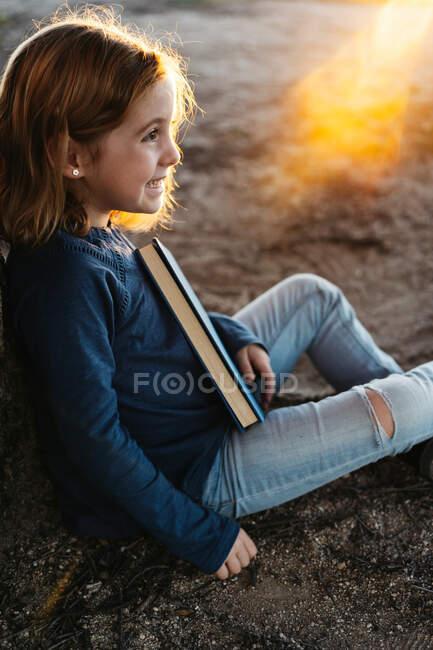 На вигляд спокійна маленька дівчинка в повсякденному одязі, віддаляючись посміхаючись, тримаючи казкову книжку, сидячи під деревом у полі в сонячний літній вечір. — стокове фото