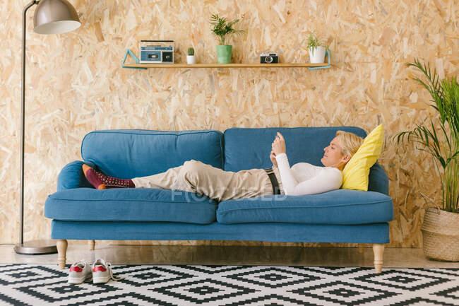 Вид сбоку на стильную блондинку-предпринимательницу, лежащую на голубом диване в современном уютном офисе с телефоном в перерыве — стоковое фото