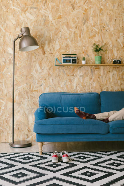 Crop businesswoman with shoes off chilling on blue soft couch during workday enjoying break — Stock Photo