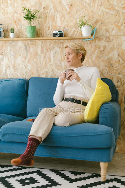 Calm thoughtful woman with short blonde hair sitting on cozy sofa in office having mug of coffee looking away — Stock Photo