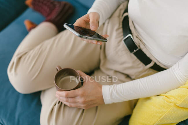 Faceless copped woman without shoes chilling on cozy sofa in office enjoying cup of coffee and surfing mobile phone — Stock Photo