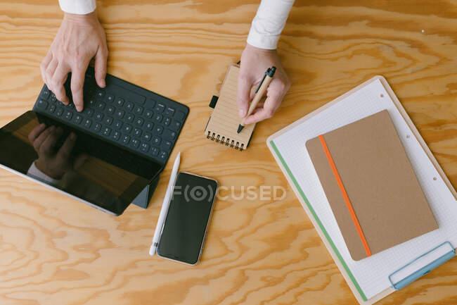 Schnittansicht einer Frau, die auf der Tastatur eines Tablets tippt, während sie Notizen in einem kleinen Notizblock auf einem Holztisch macht — Stockfoto