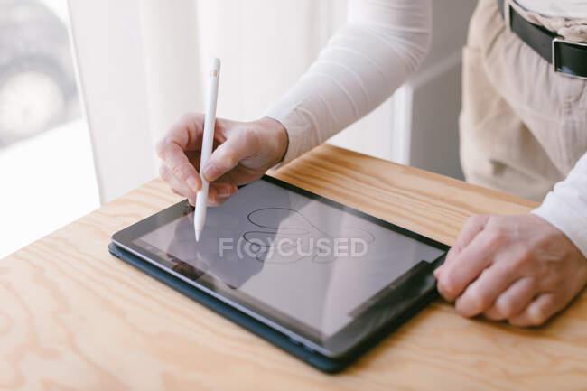 Обрезанная неузнаваемая деловая женщина, наклонившаяся над столом и работающая на планшете со стилусом в светлом деревянном офисе — стоковое фото