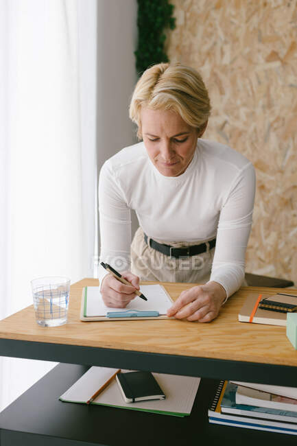 Focused adult businesswoman taking notes of plan on clipboard bending on wooden table in light office — Stock Photo