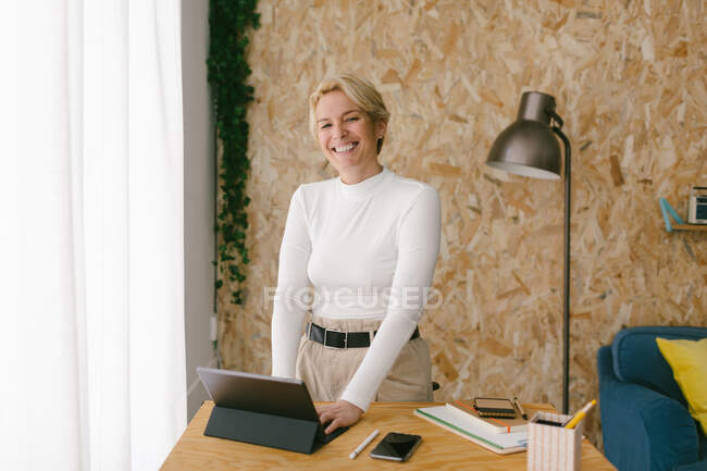 Casual modern blond businesswoman smiling looking at camera at wooden desk using tablet with keypad working in calm cozy office — Stock Photo