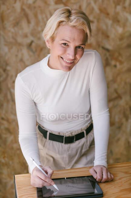 Стильная блондинка-бизнесвумен улыбается, глядя в камеру, наклоняясь над столом и работая на планшете со стилусом в светлом деревянном офисе — стоковое фото