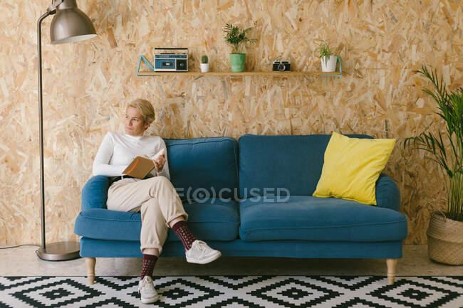 Жінка-блондинка з коротким волоссям в білій сорочці сидить на дивані і пише в блокноті, працюючи над бізнес-проектом. — стокове фото