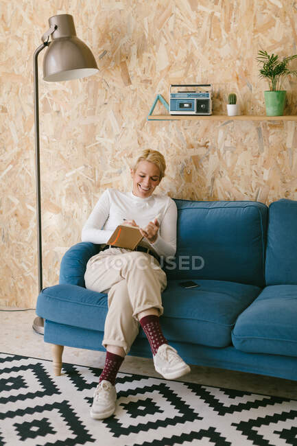 Cheerful blonde woman with short hair in white shirt sitting on sofa and writing in notebook working on business project — Stock Photo