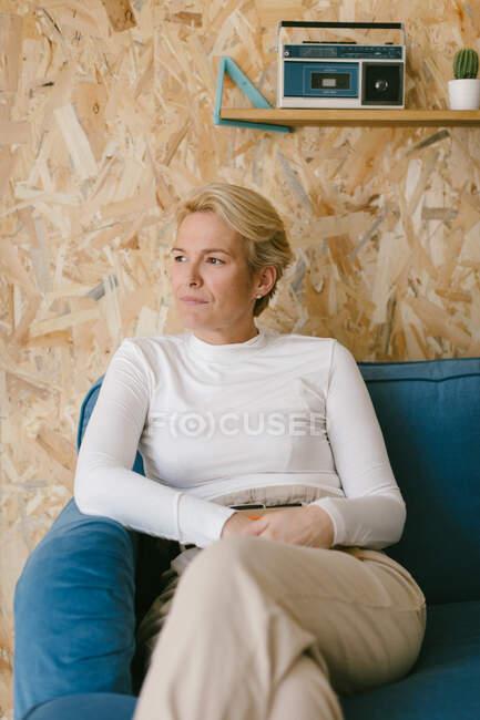 Mulher de negócios adulta alegre em camisa branca olhando embora enquanto descansa no sofá azul no escritório — Fotografia de Stock