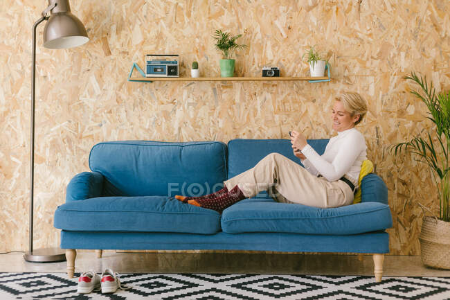 Side view of casual woman texting on smartphone while having break in office sitting on sofa — Stock Photo