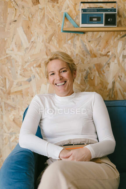 Cheerful adult businesswoman in white shirt smiling brightly at camera while resting on blue sofa in office — Stock Photo