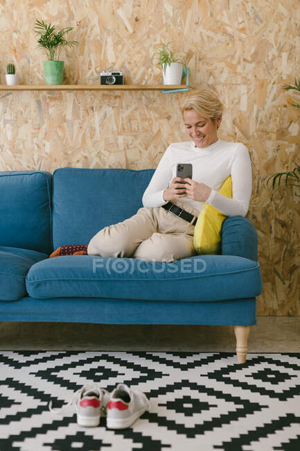 Side view of casual cheerful woman texting on smartphone while having break in office sitting on sofa — Stock Photo