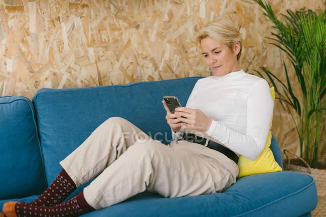 Vue latérale de femme occasionnelle textos sur smartphone tout en ayant pause dans le bureau assis sur le canapé — Photo de stock