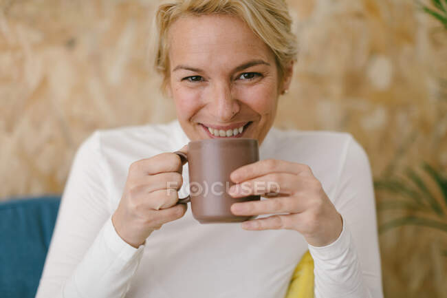 Calm adult businesswoman with short blonde hair sitting on cozy sofa in office having mug of coffee and smiling calmly at camera — Stock Photo