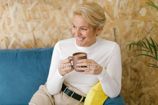Calm adult businesswoman with short blonde hair sitting on cozy sofa in office having mug of coffee and smiling calmly looking away — Stock Photo