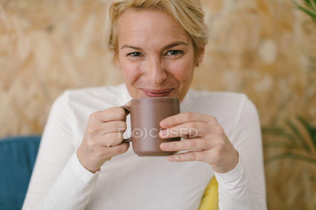 Femme d'affaires adulte calme avec des cheveux blonds courts assis sur un canapé confortable dans le bureau ayant tasse de café et souriant calmement à la caméra — Photo de stock