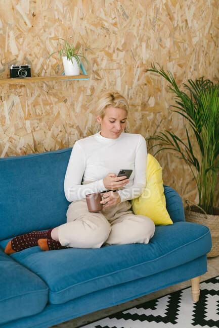Blonde Geschäftsfrau mit kurzen Haaren ohne Schuhe chillt auf gemütlichem Sofa im Büro und genießt Tasse Kaffee und surfendes Handy — Stockfoto