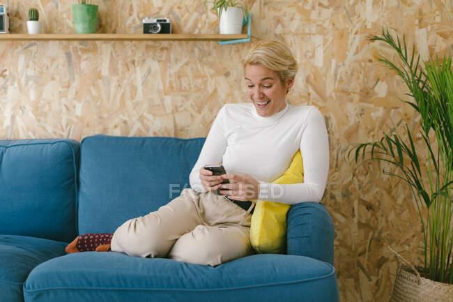 Блондинка-бизнесвумен с короткими волосами без обуви, отдыхающая на уютном диване в офисе, наслаждаясь чашечкой кофе и серфингом на мобильном телефоне — стоковое фото
