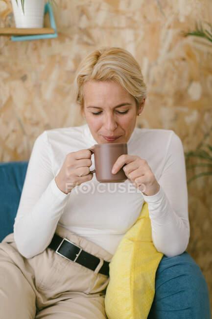 Спокойная взрослая деловая женщина с короткими светлыми волосами, сидящая на уютном диване в офисе, выпивая кружку кофе и спокойно улыбаясь, глядя в сторону — стоковое фото